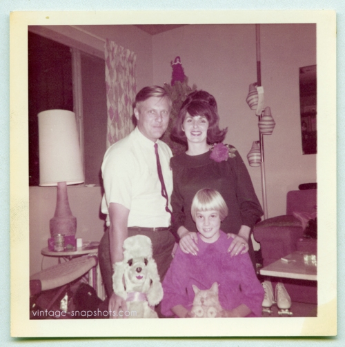 quirky odd 1960s vintage Christmas family poses with toy dog and closed-eyes cat