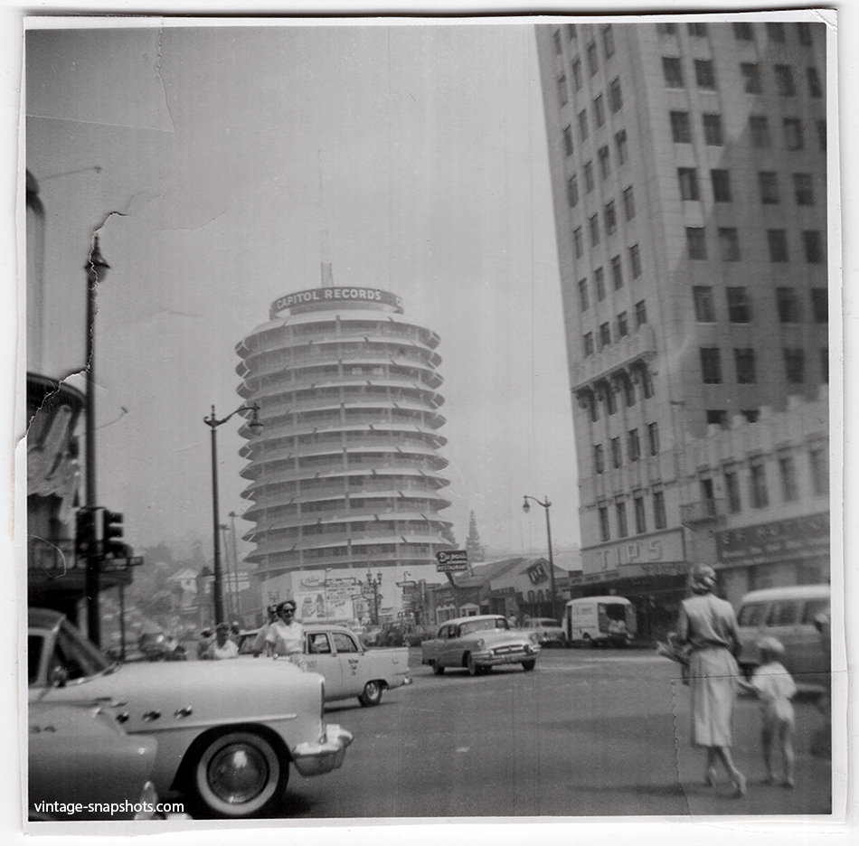 1960s snapshot of the intersection of Hollywood Blvd and Vine St, with pedestrians, traffic, shops and the Capitol Records tower